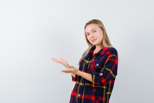Młoda dama w kraciastej koszuli wita coś i wygląda na pewną siebie, widok z przodu.