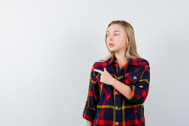 Młoda dama w kraciastej koszuli wskazująca na lewą stronę i wyglądająca na pewną siebie, widok z przodu.