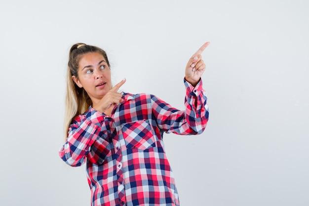 Młoda dama w kraciastej koszuli wskazująca na prawy górny róg i wyglądająca na zaciekawioną, widok z przodu.