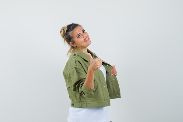 Młoda dama w kurtce t-shirt pokazując kciuk w górę, ciągnąc kurtkę i wyglądając pewnie