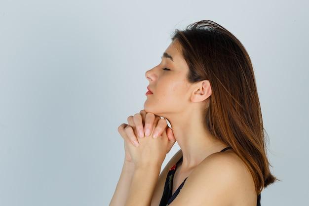 Młoda dama w kwiecistej bluzce trzymająca się za ręce pod brodą i wyglądająca na zdziwioną