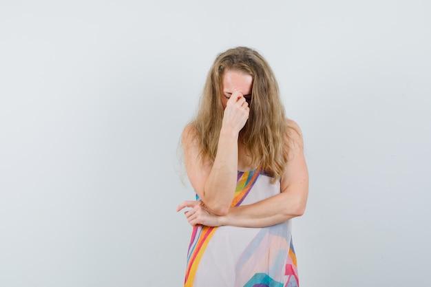 Młoda dama w letniej sukience przeciera oczy i nos i wygląda na wyczerpaną