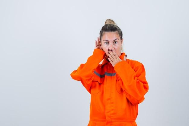 Młoda dama w mundurze pracownika, słuchanie i patrząc zaskoczony, widok z przodu.