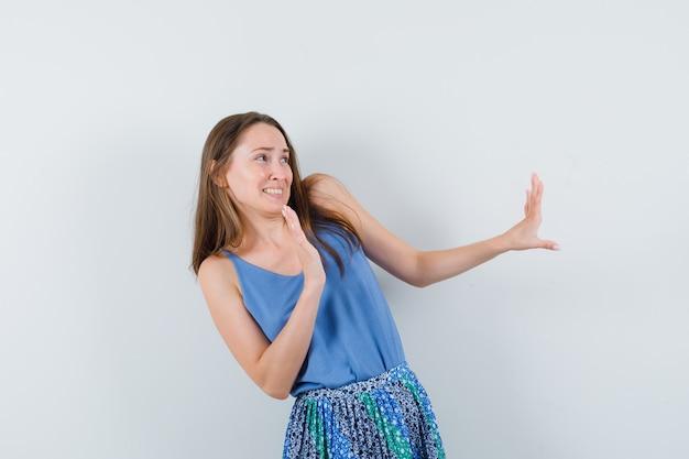 Młoda dama w niebieskiej bluzce, spódnicy podnoszącej ręce do obrony i wyglądającej na zniesmaczoną, widok z przodu.
