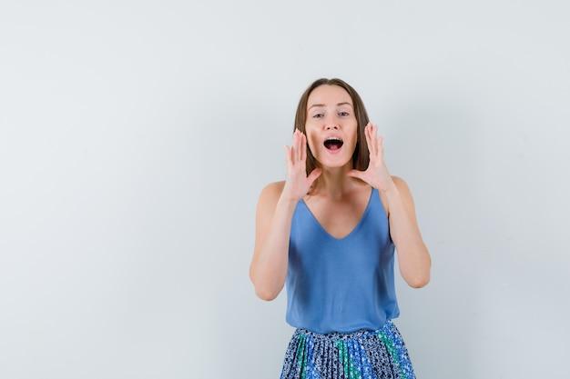 Młoda dama w niebieskiej bluzce, spódnicy wzywającej kogoś donośnym głosem, widok z przodu.