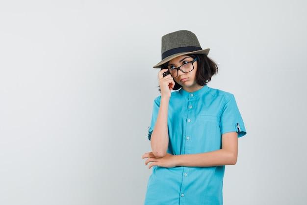 Młoda dama w niebieskiej koszuli, kapeluszu, okularach, patrząc przez okulary i patrząc uważnie