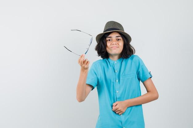 Młoda dama w niebieskiej koszuli, kapeluszu, okularach przeciwsłonecznych pokazuje bezradny gest trzymając okulary