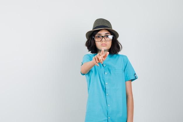 Młoda dama w niebieskiej koszuli, kapeluszu, okularach, wskazująca na przód i uważna