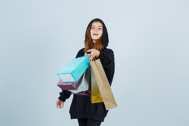 Młoda dama w obszernej bluzie z kapturem, spodniach pokazujących gest, trzymając paczki i wyglądająca na szczęśliwą, widok z przodu.