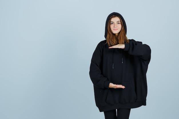 Młoda dama w obszernej bluzie z kapturem, spodniach ze znakiem rozmiaru i pewnej siebie, widok z przodu.