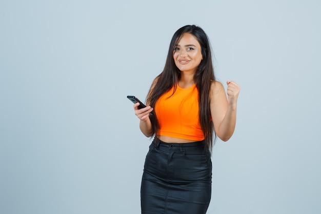 Młoda dama w podkoszulku, mini spódniczce podnosząca pięść, patrząc na kamerę i wyglądająca błogo, widok z przodu.