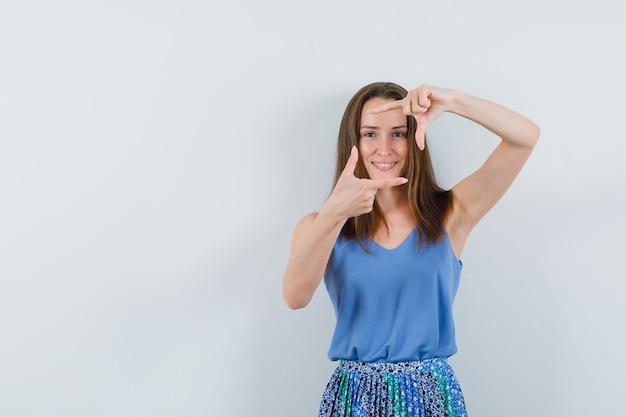 Młoda dama w podkoszulku, spódnicy robi gest ramy i wygląda wesoło