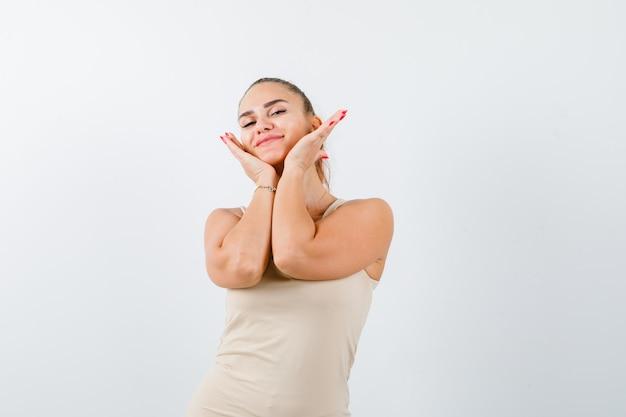 Młoda dama w podkoszulku trzyma ręce pod brodą i wygląda wdzięcznie, widok z przodu.