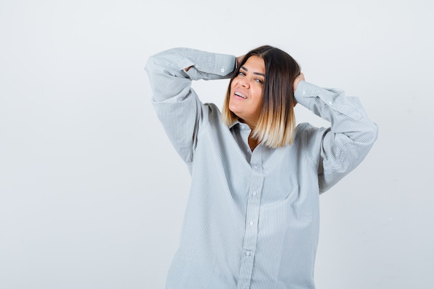 Młoda dama w ponadgabarytowej koszuli trzymając się za ręce na głowie i patrząc na szczęśliwego, widok z przodu.