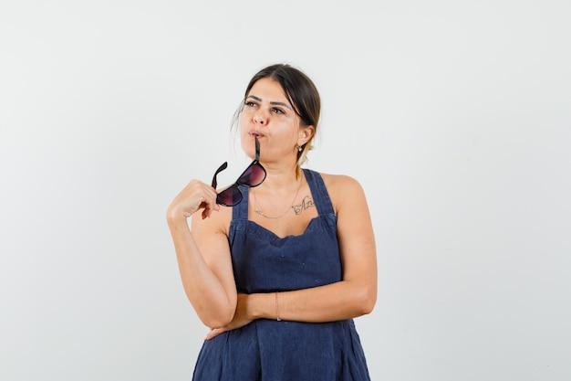 Młoda dama w sukience gryzie okulary i wygląda na zamyśloną