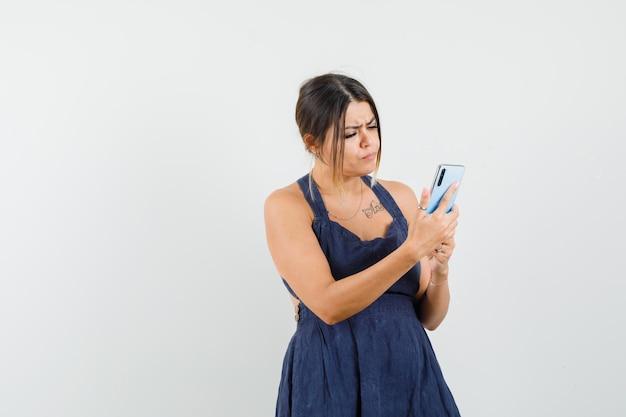 Młoda dama w sukience korzysta z telefonu komórkowego i wygląda na zajętą