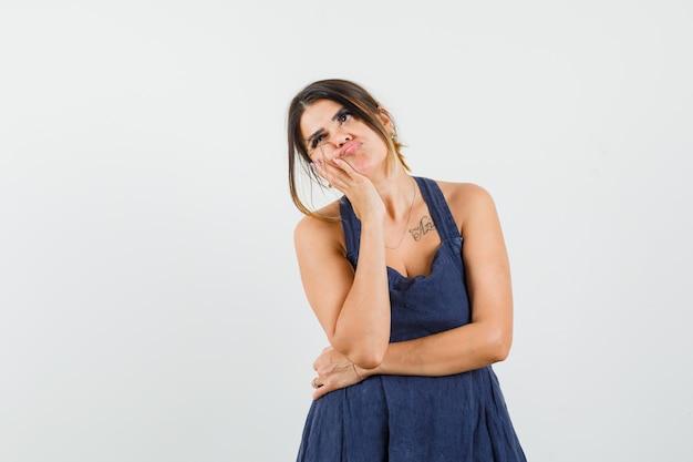 Młoda dama w sukience opiera policzek na dłoni i wygląda na zamyśloną