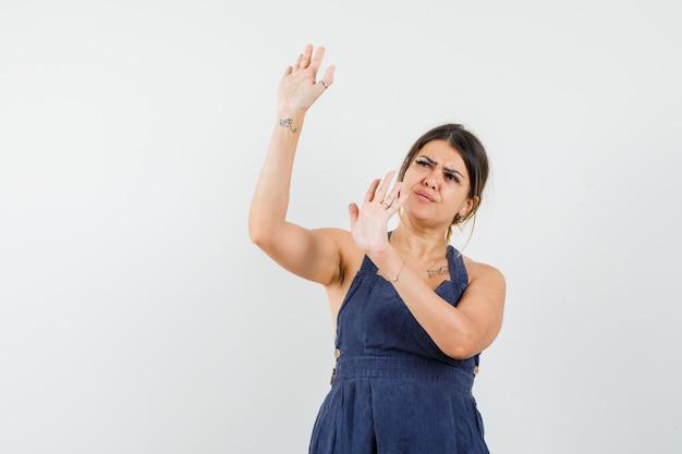 Młoda dama w sukience podnosi ręce, by się bronić i wygląda na przestraszoną