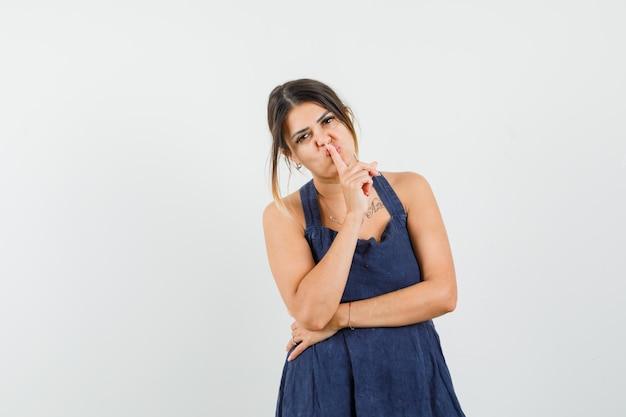 Młoda dama w sukience pokazująca gest ciszy i wyglądająca ostrożnie