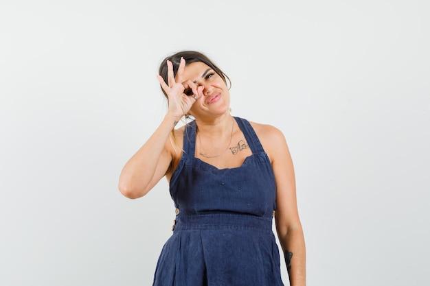Młoda dama w sukience pokazująca znak ok na oku