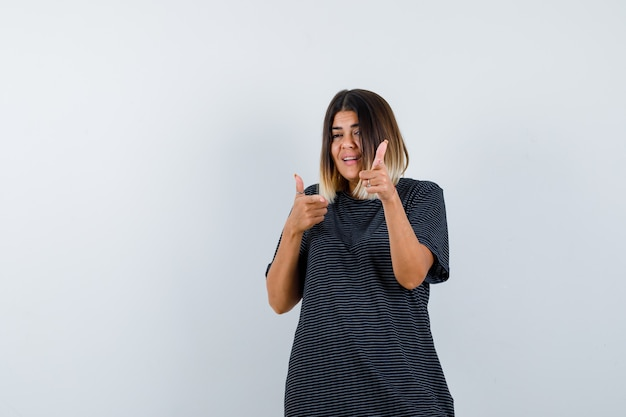 Młoda dama w sukience polo, wskazując na aparat i patrząc szczęśliwy, widok z przodu.