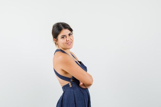 Młoda dama w sukni stoi ze skrzyżowanymi rękami i wygląda pewnie.