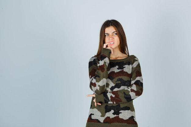 Młoda dama w swetrze gryzie paznokcie i wygląda zamyślona