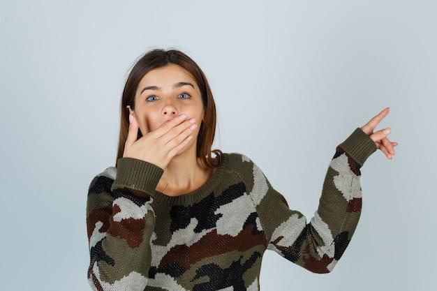 Młoda dama w swetrze, spódnica wskazująca na prawy górny róg, trzymając dłoń na ustach