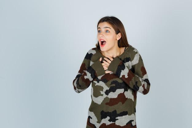 Młoda dama w swetrze, spódnicy, trzymając ręce na piersi i wyglądająca na zaskoczoną