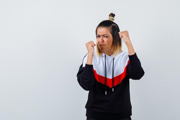 Młoda dama w swetrze z kapturem stojąca w pozie do walki i wyglądająca na pewną siebie