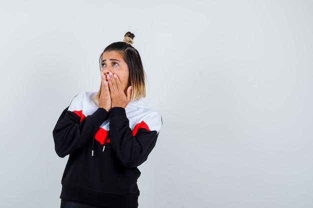 Młoda dama w swetrze z kapturem trzyma ręce na ustach i wygląda na zdziwioną