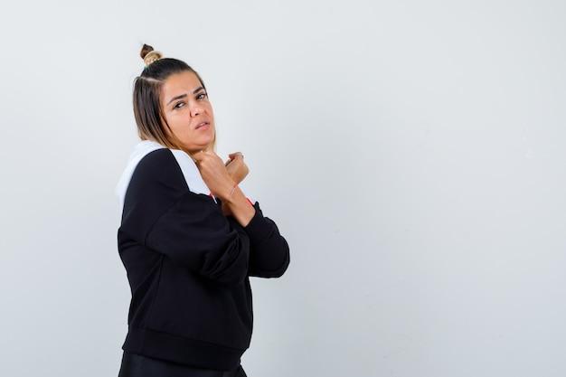 Młoda dama w swetrze z kapturem, trzymająca skrzyżowane ręce na piersi i wyglądająca atrakcyjnie