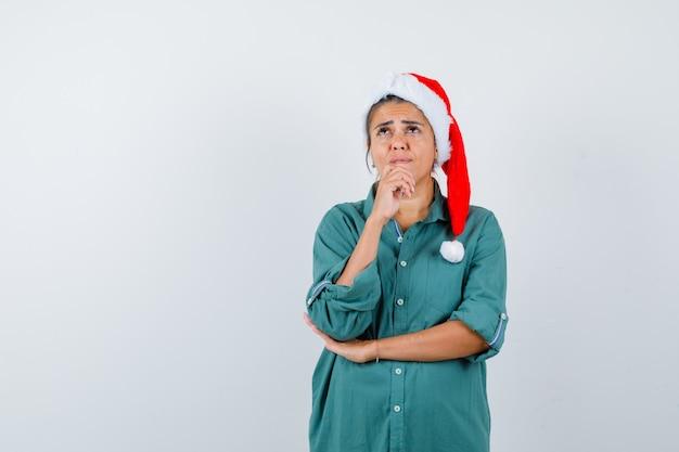 Młoda dama w świątecznym kapeluszu, koszuli i wyglądający na rozczarowany. przedni widok.