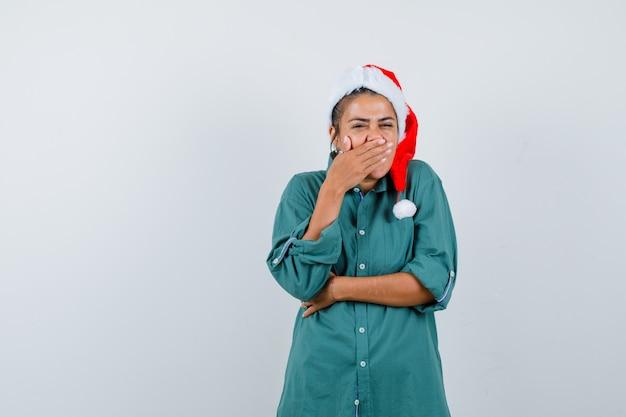 Młoda dama w świątecznym kapeluszu, koszuli z ręką na ustach i popielatym, widok z przodu.