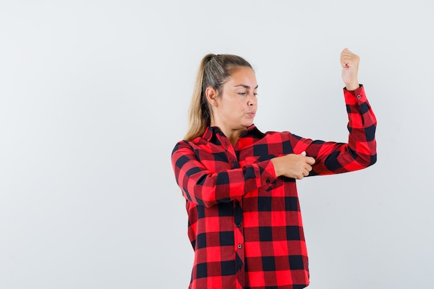 Młoda dama w swobodnej koszuli pokazuje mięśnie ramion i wygląda pewnie, widok z przodu.