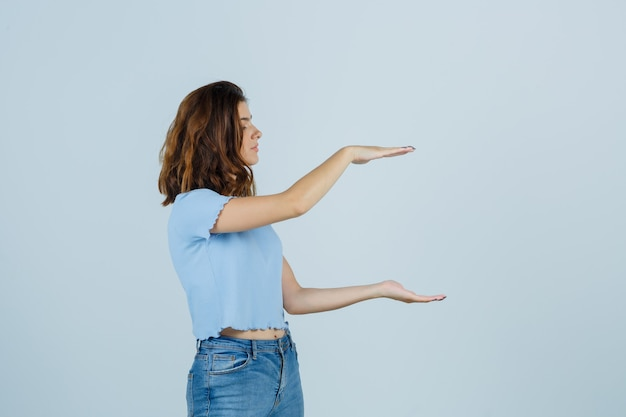 Młoda dama w t-shircie, dżinsach pokazujących duży znak rozmiaru i wyglądająca na szczęśliwą, widok z przodu.