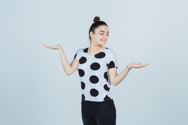 Młoda dama w t-shirt, dżinsy pokazujące gest wagi i wyglądający szczęśliwy, widok z przodu.