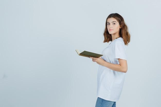 Młoda dama w t-shirt, dżinsy trzymając książkę, patrząc przez ramię i patrząc pewnie, widok z przodu.