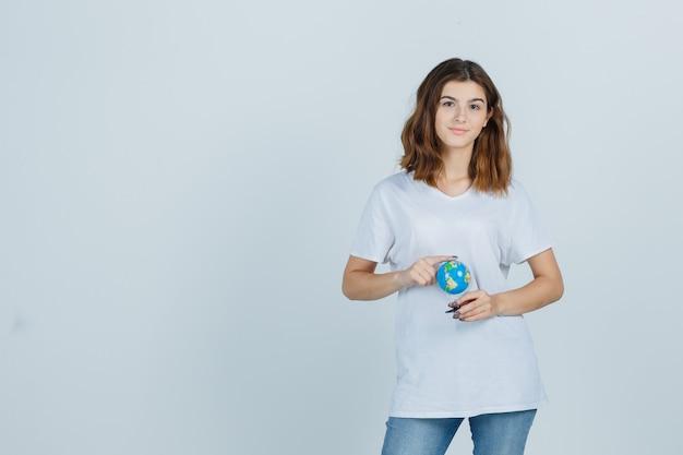 Młoda dama w t-shirt, dżinsy trzymając kulę ziemską, stojąc i patrząc pewnie, widok z przodu.