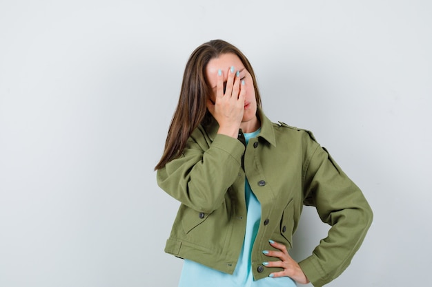 Młoda dama w t-shirt, kurtka zakrywająca twarz ręką, trzymając rękę na biodrze i patrząc zapominalski, widok z przodu.