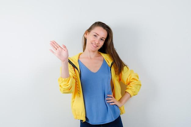 Młoda dama w t-shirt, marynarka macha ręką na powitanie i wygląda wspaniale