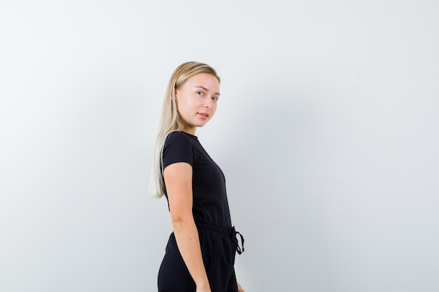 Młoda dama w t-shirt, spodnie, patrząc na kamery, pozując i patrząc ponętnie, widok z przodu.