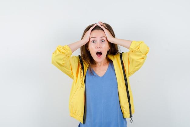 Młoda dama w t-shirt, trzymając głowę w dłoniach i patrząc podekscytowany, widok z przodu.