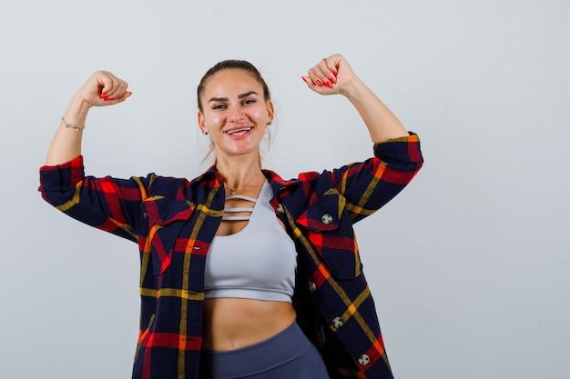Młoda dama w top, koszula w kratę pokazująca gest zwycięzcy i patrząca na szczęście, widok z przodu.