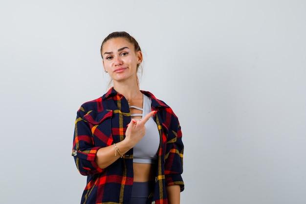 Młoda dama w topie, koszula w kratę, wskazująca na prawy górny róg i wyglądająca ładnie, widok z przodu.