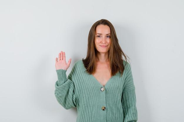 Młoda dama w wełnianym swetrze macha ręką na powitanie i wygląda pewnie, widok z przodu.