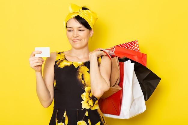 Młoda dama w widoku z przodu, w żółto-czarnym kwiatowym stroju z żółtym bandażem na głowie, trzymająca paczki z zakupami na żółtym