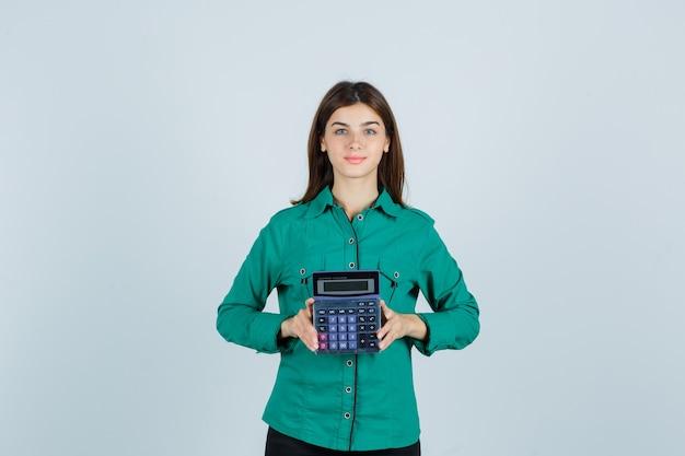 Młoda dama w zielonej koszuli trzyma kalkulator i wygląda pewnie, widok z przodu.