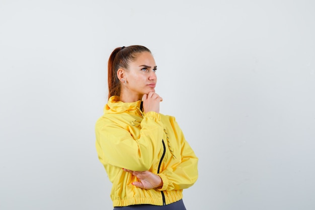 Młoda dama w żółtej kurtce podpierająca podbródek pod ręką i patrząc zamyślony, widok z przodu.