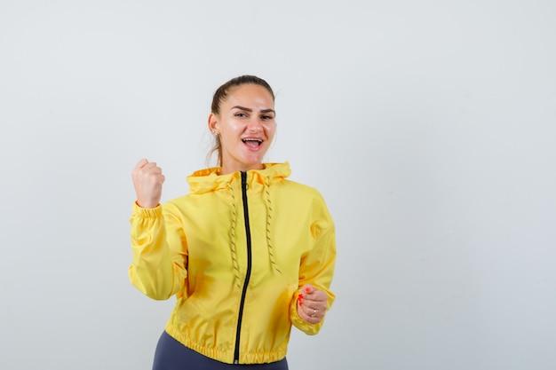 Młoda dama w żółtej kurtce pokazując gest zwycięzcy i patrząc na szczęście, widok z przodu.